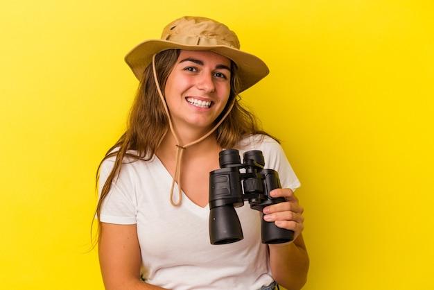 Молодая кавказская женщина, держащая бинокль на желтом фоне, смеется и веселится.