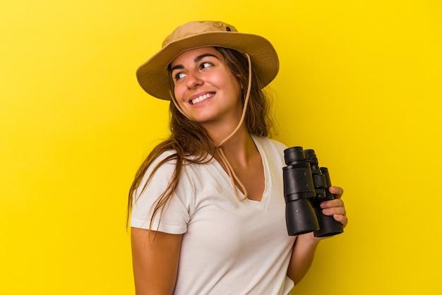 Молодая кавказская женщина, держащая бинокль на желтом фоне, смотрит в сторону, улыбаясь, веселая и приятная.