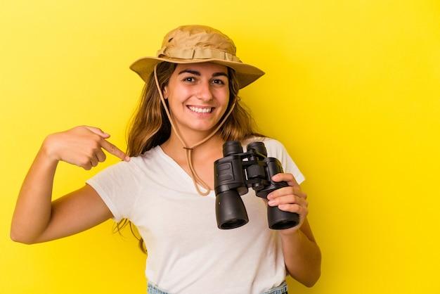 Молодая кавказская женщина, держащая бинокль на желтом фоне, человек, указывая рукой на пространство для копирования рубашки, гордый и уверенный