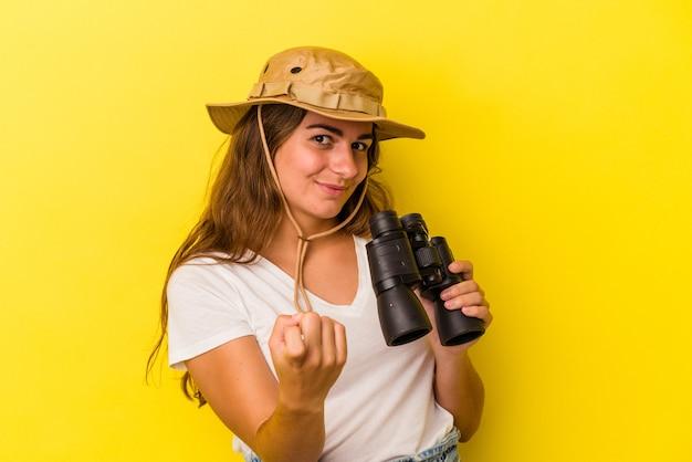 Молодая кавказская женщина, держащая бинокль на желтом фоне, указывая пальцем на вас, как будто приглашая подойти ближе.