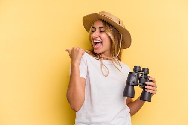 Молодая кавказская женщина, держащая бинокль на желтом фоне, указывает пальцем, смеясь и беззаботно.