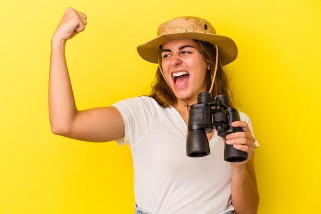 Молодая кавказская женщина, держащая бинокль на желтом фоне, поднимая кулак после победы, концепции победителя.