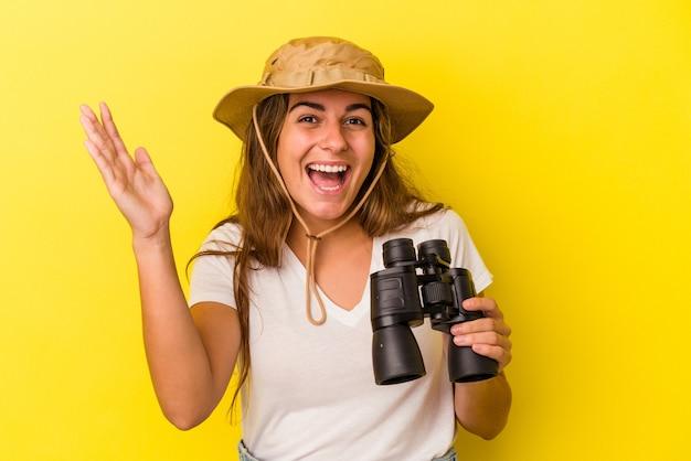 Молодая кавказская женщина держит бинокль на желтом фоне, получая приятный сюрприз, возбужденный и поднимающий руки.