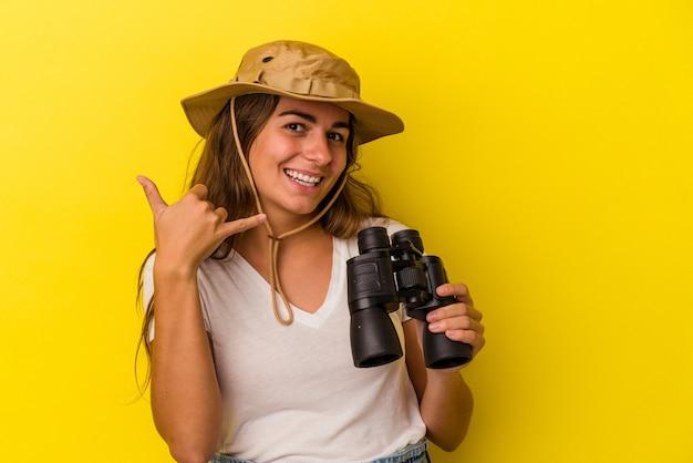 Молодая кавказская женщина, держащая бинокль на желтом фоне, показывая жест мобильного телефона пальцами.