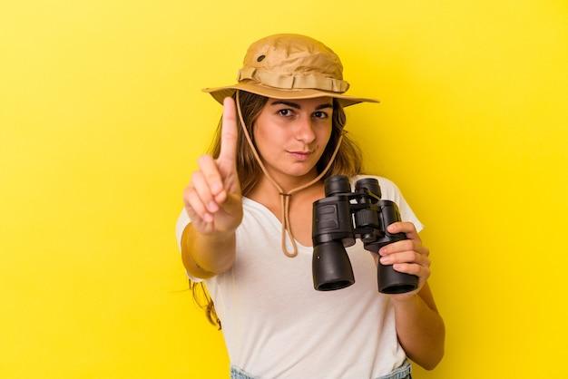 Молодая кавказская женщина, держащая бинокль на желтом фоне, показывает номер один пальцем.