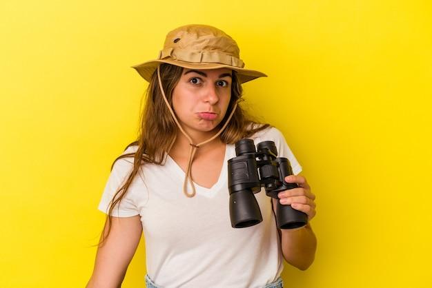 Молодая кавказская женщина, держащая бинокль на желтом фоне, пожимает плечами и смущает открытые глаза.