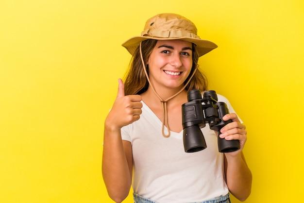 Молодая кавказская женщина, держащая бинокль на желтом фоне, улыбается и поднимает палец вверх