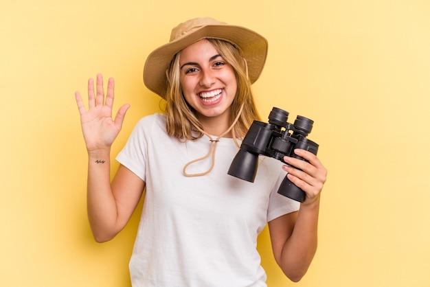 Молодая кавказская женщина, держащая бинокль на желтом фоне, улыбается веселый, показывая номер пять с пальцами.
