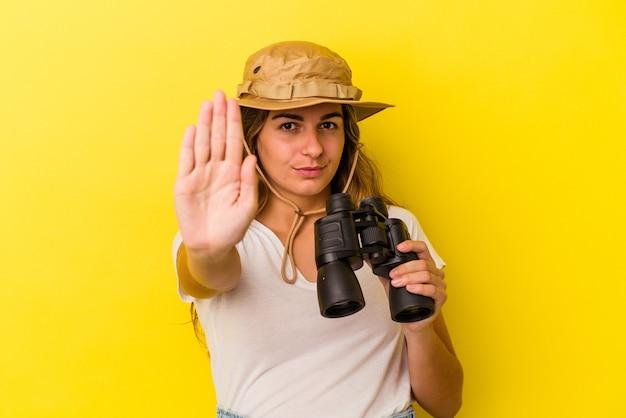 黄色の背景に分離された双眼鏡を持っている若い白人女性は、一時停止の標識を示している手を伸ばして立って、あなたを妨げています。