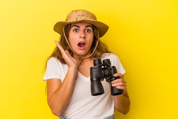 Молодая кавказская женщина, держащая бинокль на желтом фоне, удивлена и шокирована.