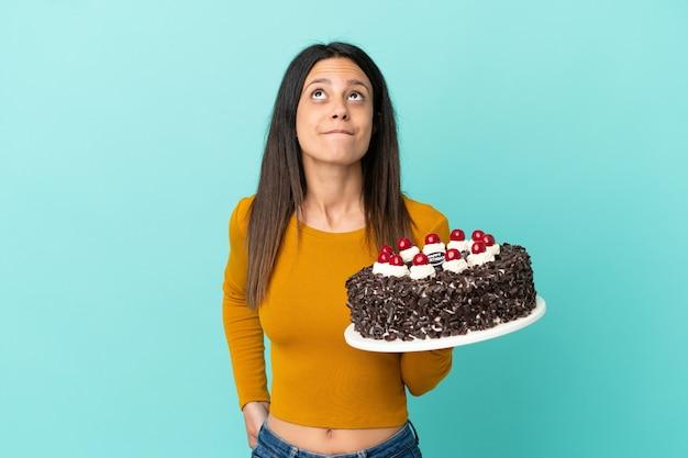 青い背景で隔離の誕生日ケーキを保持し、見上げる若い白人女性