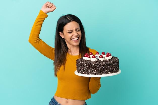 勝利を祝って青い背景で隔離のバースデーケーキを保持している若い白人女性