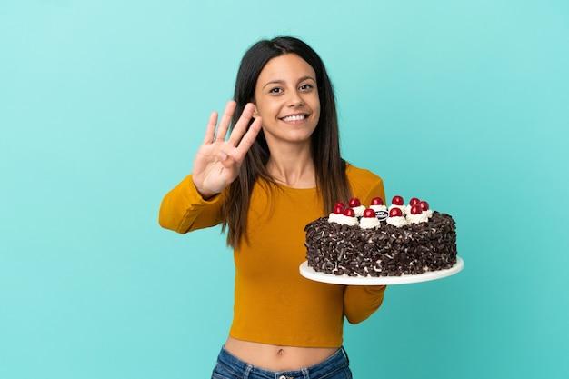 幸せな青い背景で隔離の誕生日ケーキを保持し、指で4を数える若い白人女性