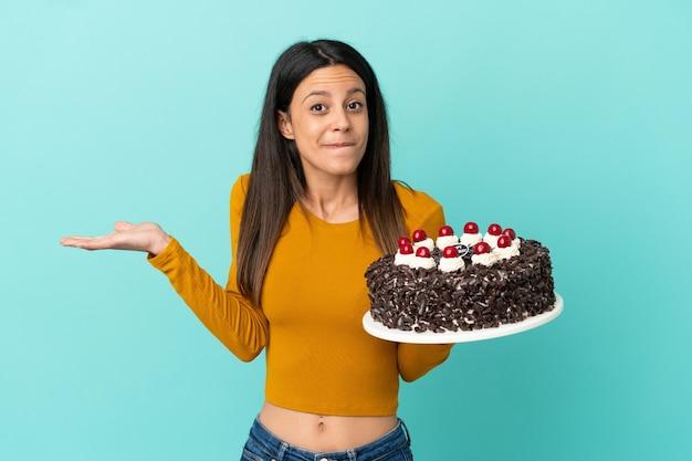 手を上げている間疑いを持っている青い背景で隔離のバースデーケーキを保持している若い白人女性