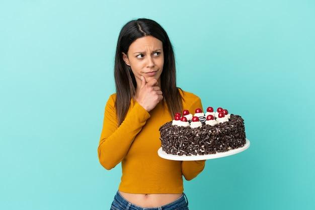 Молодая кавказская женщина, держащая торт ко дню рождения изолирована на синем фоне, сомневаясь