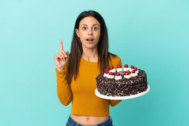 Молодая кавказская женщина держит торт ко дню рождения изолирована на синем фоне, намереваясь реализовать решение, подняв палец вверх