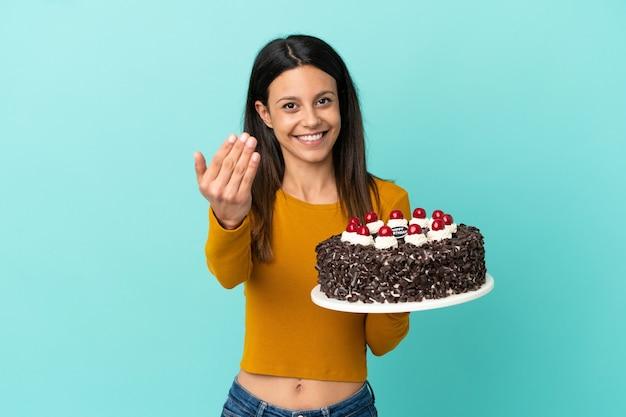 Молодая кавказская женщина держит торт ко дню рождения, изолированные на синем фоне, приглашая прийти с рукой. счастлив что ты пришел