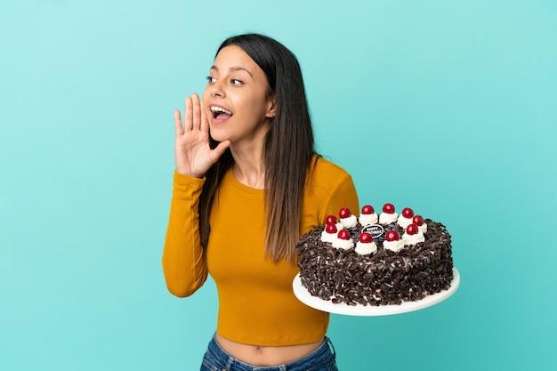 Молодая кавказская женщина, держащая торт ко дню рождения изолирована на синем фоне, кричит с широко открытым ртом в сторону