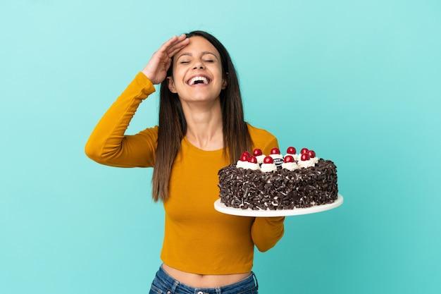 Молодая кавказская женщина держит торт ко дню рождения, изолированные на синем фоне, много улыбаясь