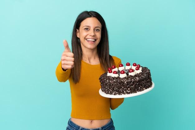 Молодая кавказская женщина держит торт ко дню рождения изолирована на синем фоне с большими пальцами руки вверх, потому что произошло что-то хорошее