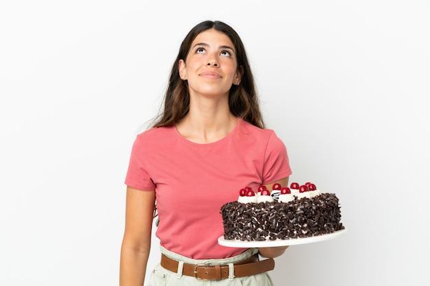 Молодая кавказская женщина держит торт ко дню рождения на белом фоне и смотрит вверх