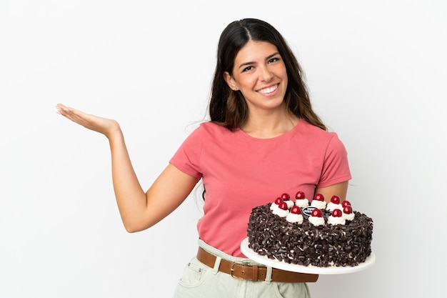 白い背景で隔離の誕生日ケーキを保持している若い白人女性は、来て招待するために手を横に伸ばします