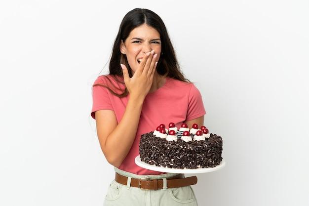 白い背景で隔離の誕生日ケーキを保持している若い白人女性幸せと笑顔の手で口を覆う