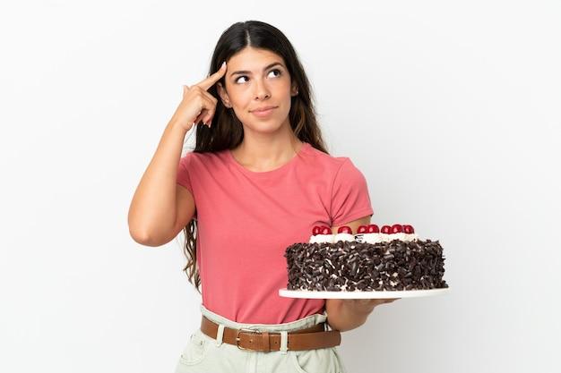 Молодая кавказская женщина держит праздничный торт на белом фоне, сомневаясь и думая