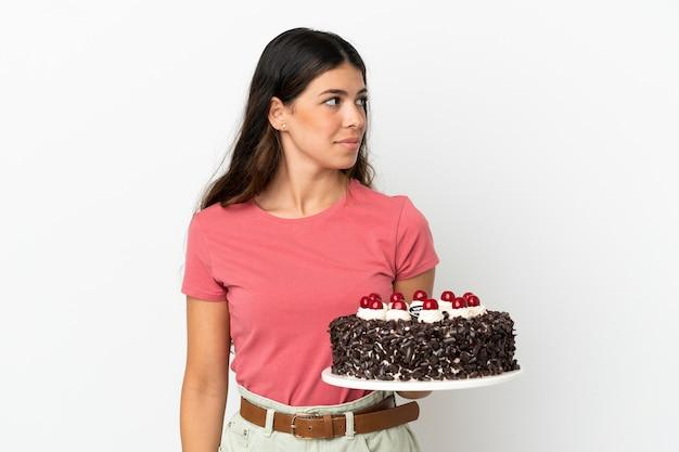 Молодая кавказская женщина держит праздничный торт на белом фоне, глядя в сторону