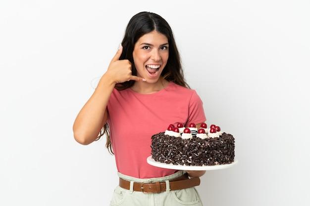 Молодая кавказская женщина, держащая торт ко дню рождения, изолированные на белом фоне, делая телефонный жест. перезвони мне знак