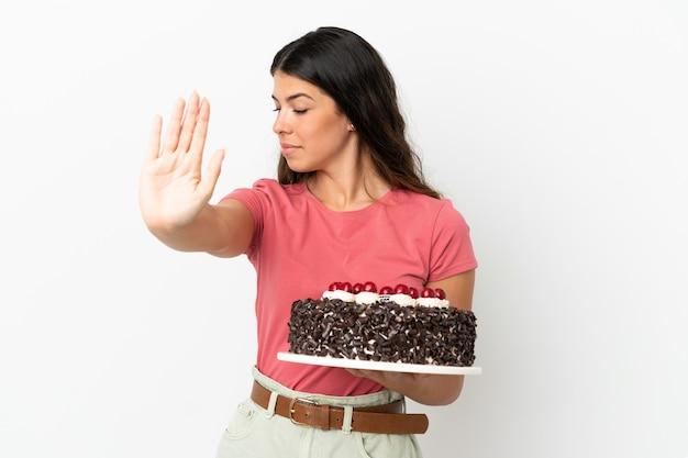 Молодая кавказская женщина держит праздничный торт на белом фоне, делая жест стоп и разочарована