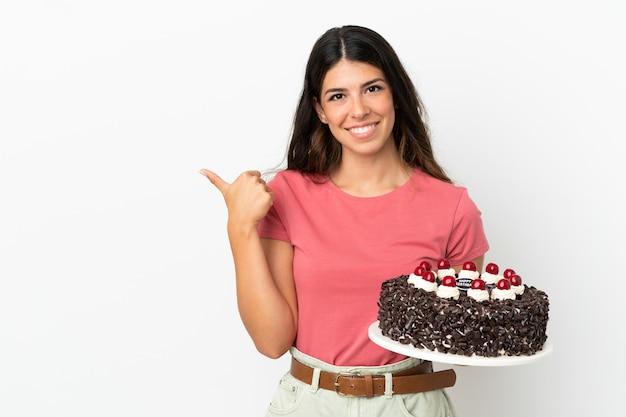 Молодая кавказская женщина держит праздничный торт на белом фоне, указывая в сторону, чтобы представить продукт