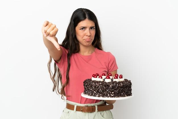 Молодая кавказская женщина держит праздничный торт на белом фоне, показывая большой палец вниз с отрицательным выражением лица
