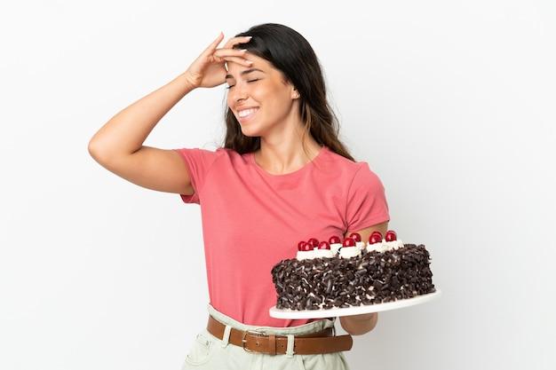Молодая кавказская женщина держит торт ко дню рождения на белом фоне, много улыбаясь