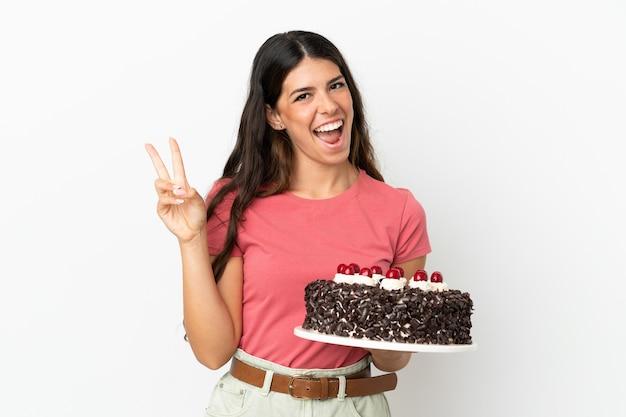 Молодая кавказская женщина держит торт ко дню рождения, изолированные на белом фоне, улыбается и показывает знак победы
