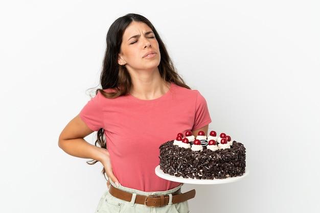 Молодая кавказская женщина держит праздничный торт на белом фоне страдает от боли в спине из-за того, что приложила усилия