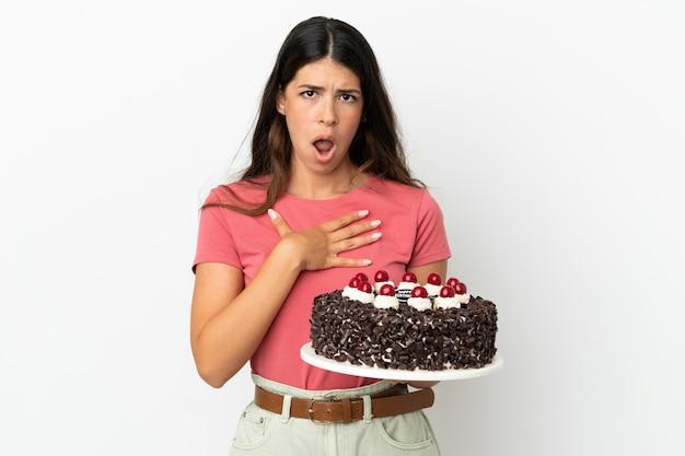 Молодая кавказская женщина, держащая праздничный торт на белом фоне, удивлена и шокирована, глядя вправо