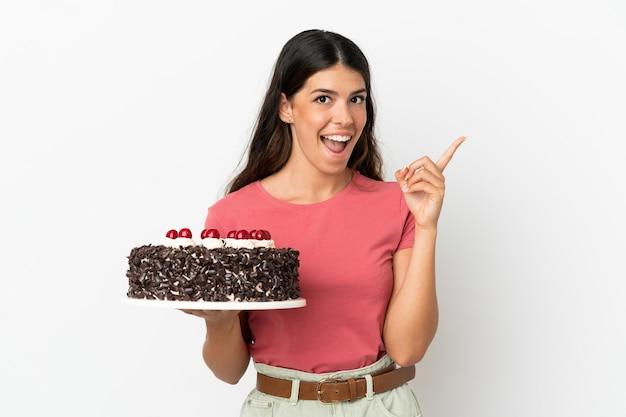 Молодая кавказская женщина держит праздничный торт на белом фоне, думая об идее, указывая пальцем вверх