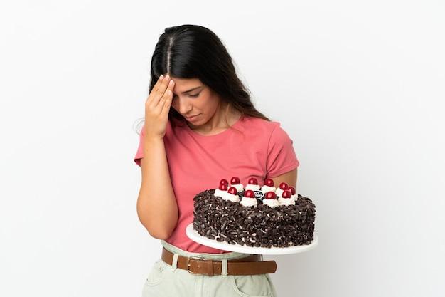 Молодая кавказская женщина держит праздничный торт на белом фоне с головной болью
