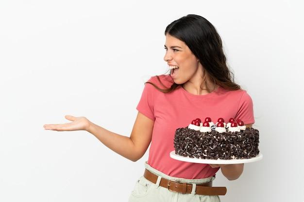Молодая кавказская женщина держит праздничный торт на белом фоне с удивленным выражением лица, глядя в сторону
