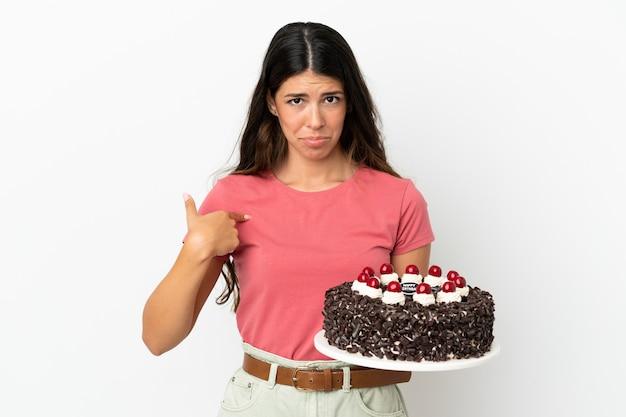 Молодая кавказская женщина держит праздничный торт на белом фоне с удивленным выражением лица