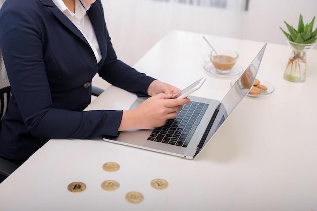Молодая кавказская женщина держит биткойн на офисном столе и печатает на смартфоне