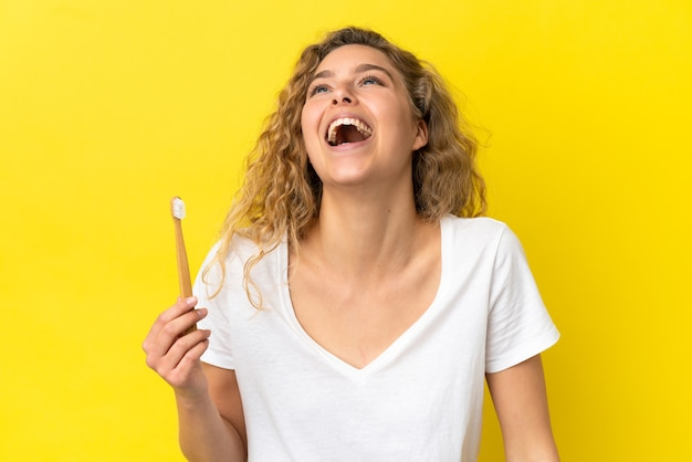 Young caucasian woman holding a brushing teeth isolated on yellow background laughing