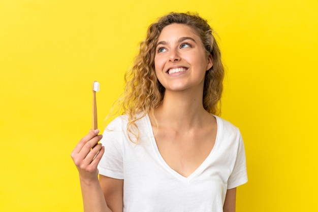 Young caucasian woman holding a brushing teeth isolated on yellow background thinking an idea while looking up