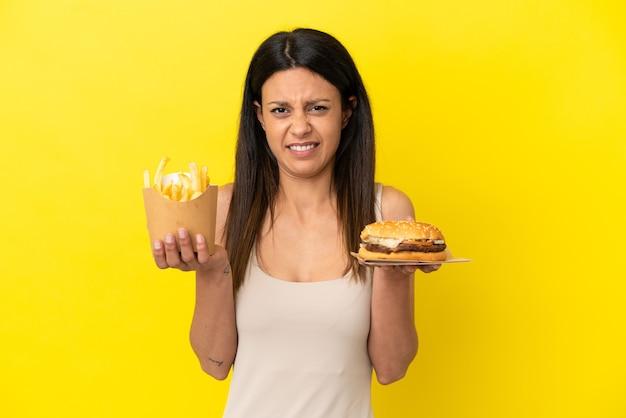 黄色の背景で隔離のハンバーガーとチップを保持している若い白人女性