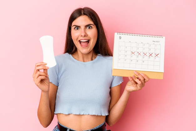 Young caucasian woman holding a calendar and a compress isolated on pink background