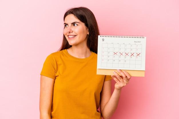 분홍색 배경에 고립 된 달력을 들고 젊은 백인 여자는 옆으로 웃 고, 명랑 하 고 즐거운 보인다.