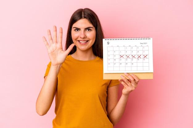 분홍색 배경에 고립 된 달력을 들고 젊은 백인 여자 손가락으로 명랑 보여주는 번호 5를 웃 고.