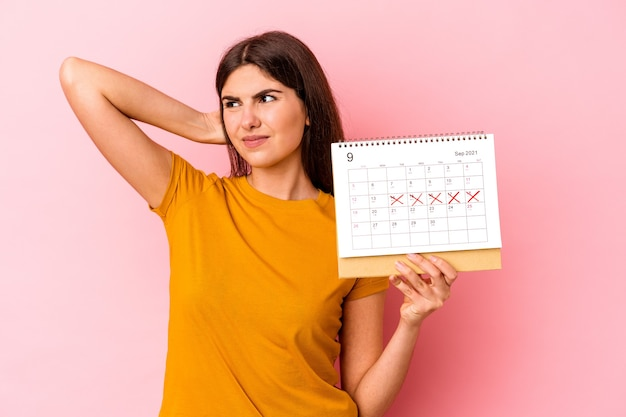 頭の後ろに触れて、考えて、選択をするピンクの背景に分離されたカレンダーを保持している若い白人女性。