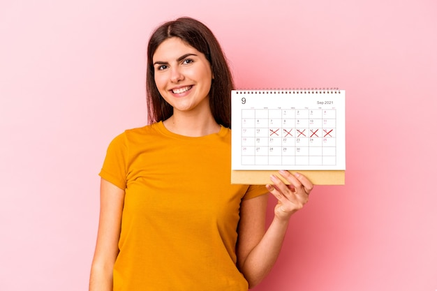 행복하고, 웃고, 쾌활한 분홍색 벽에 고립 된 달력을 들고 젊은 백인 여자